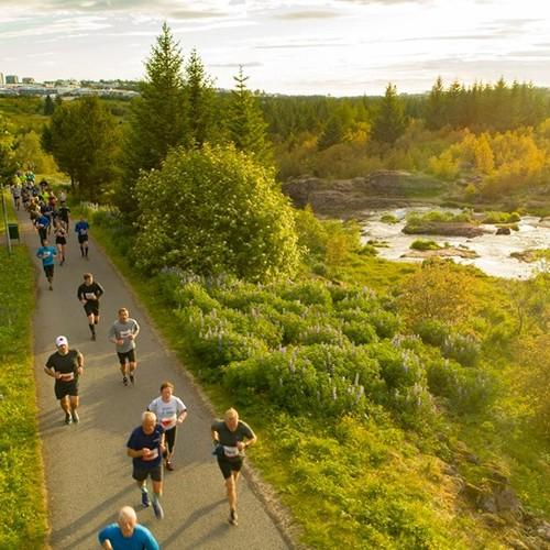 Participants running in the midnight sun at Elliðaárdalur valley