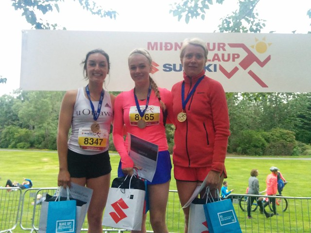 Three female runners with their prizes